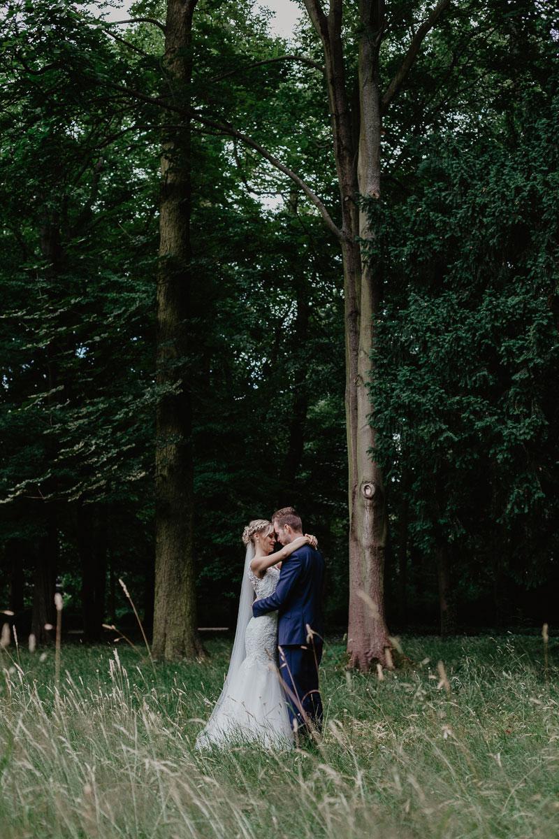 Brautpaar steht auf einer wilden Wiese und umarmt sich